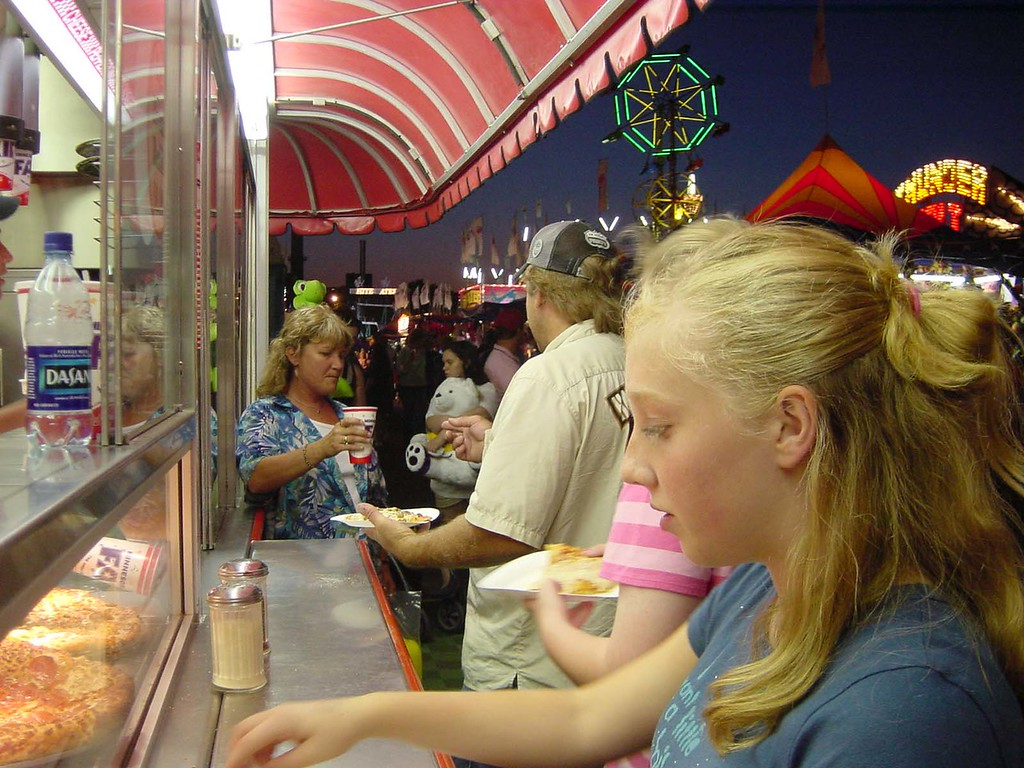 . Farigoers purchase pizza at a concession in the Mighty Midway / carnival at night during the 2005 Minnesota State Fair. Photo courtesy of the Minnesota State Fair.