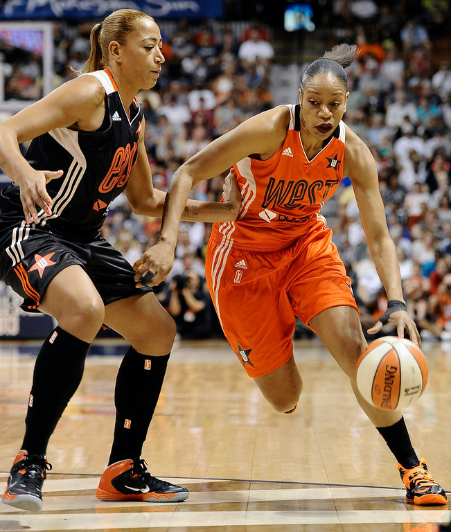. East\'s Erika de Souza, left, of the Atlanta Dream, guards West\'s Tina Thompson, of the Seattle Storm, during the first half. (AP Photo/Jessica Hill)