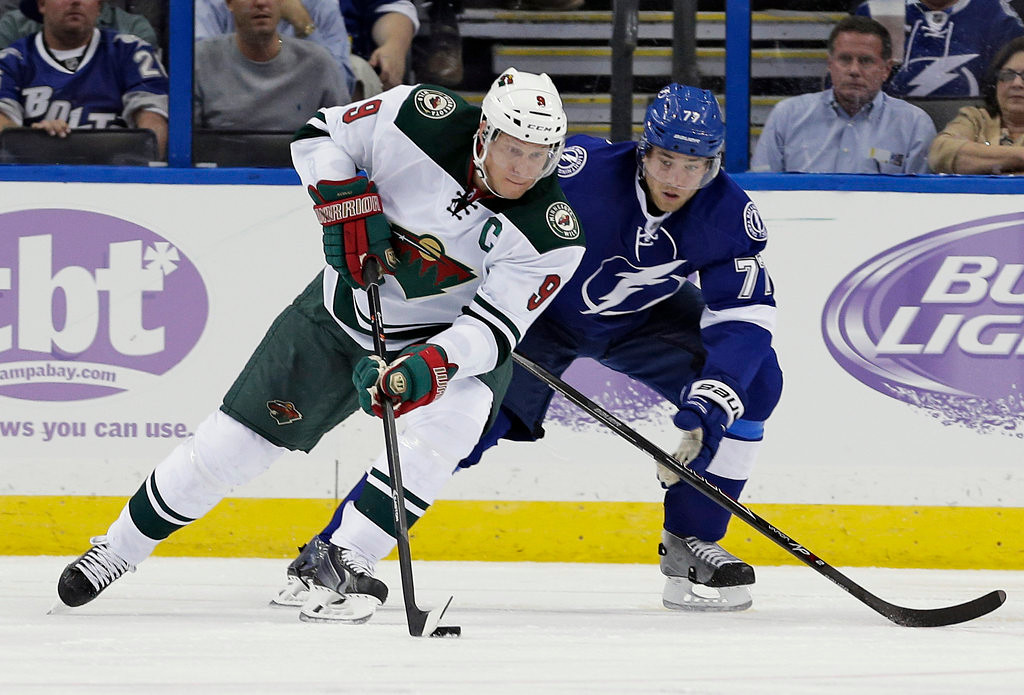 . Minnesota Wild center Mikko Koivu (9), of Finland, moves the puck around Tampa Bay Lightning defenseman Victor Hedman (77), of Sweden, during the second period of an NHL hockey game Thursday, Oct. 17, 2013, in Tampa, Fla. (AP Photo/Chris O\'Meara)