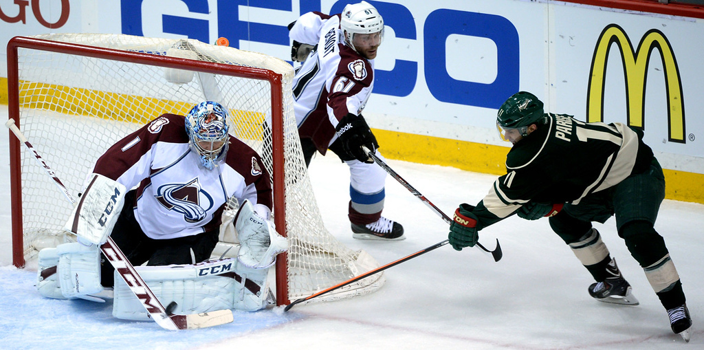 . Minnesota\'s Zach Parise, right, tries to tuck the puck past Colorado goalie Semyon Varlamov during the first period. Avs defenseman Andre Benoit follows the play behind the net.  (Pioneer Press: Sherri LaRose-Chiglo)