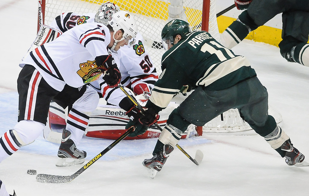 . Minnesota left wing Zach Parise, right, scrambles for the puck in front of the net with Chicago center Jonathan Toews, left and Chicago goalie Corey Crawford in the second period. (Pioneer Press: Ben Garvin)