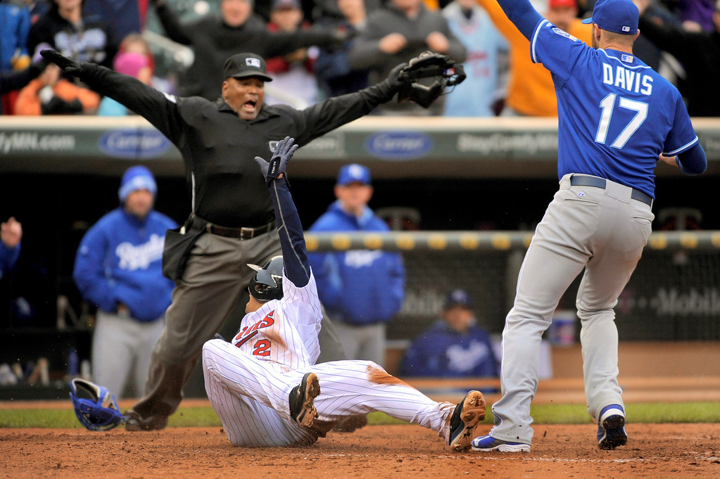 . Minnesota Twins Brian Dozier, left front, looks back as home plate umpire Laz Diaz, back left, makes the safe call while Kansas City Royals pitcher Wade Davis looks for the call during the ninth inning of a baseball game in Minneapolis, Sunday, April 13, 2014. Minnesota won 4-3. (AP Photo/Tom Olmscheid)