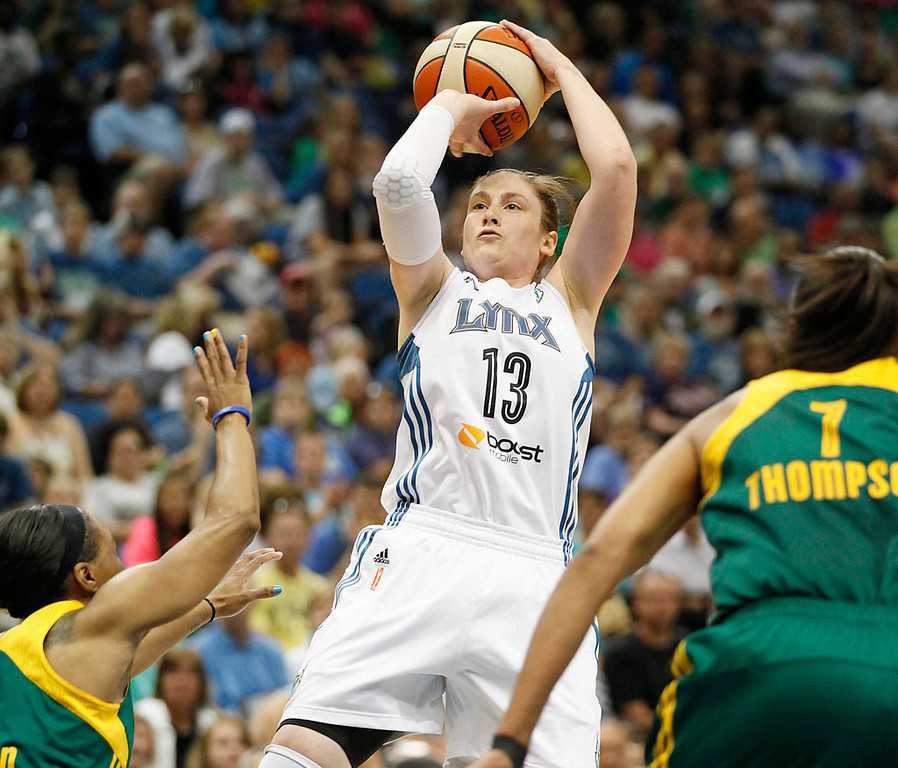 . Minnesota Lynx guard Lindsay Whalen (13) falls back for a shot against  Seattle Storm guard Temeka Johnson (2) forward Tina Thompson (7) in the first half of a WNBA basketball game, Sunday, Aug. 4, 2013, in Minneapolis. (AP Photo/Stacy Bengs)