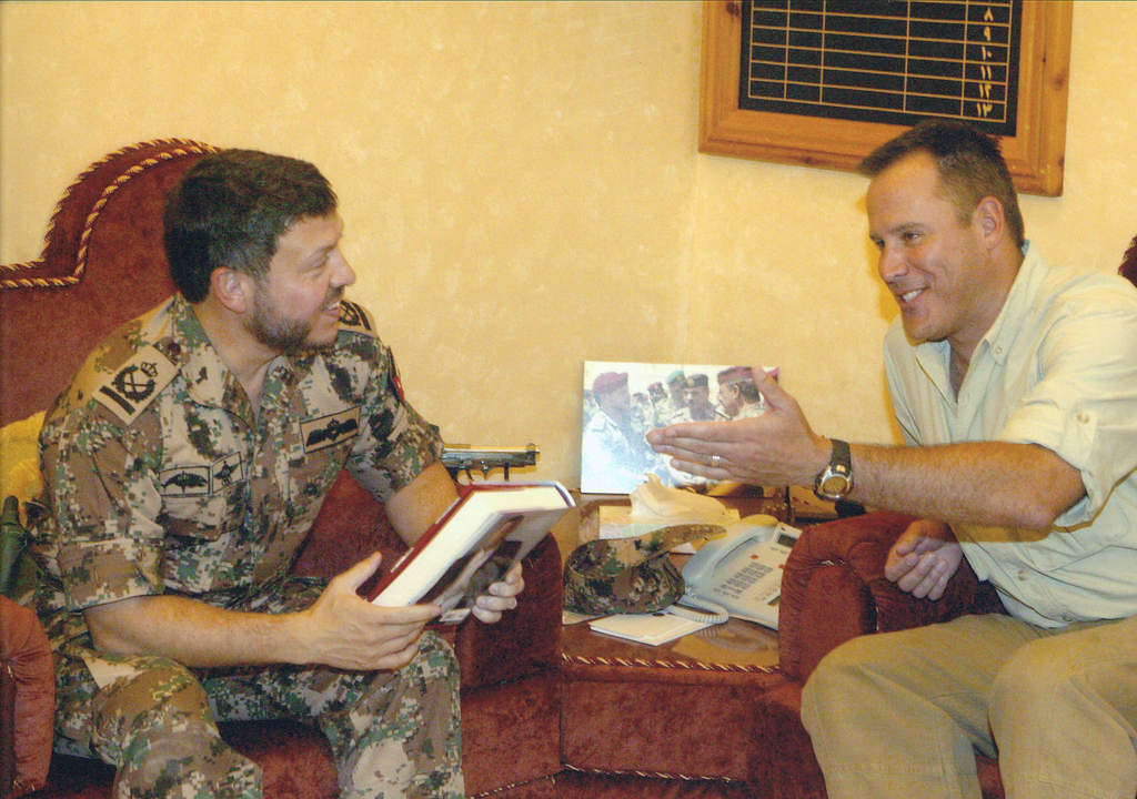 """. Flynn, right, presents Jordanian King Abdullah II a copy of his latest book at the time, the 2005-published \""""Consent To Kill,\"""" during a trip to Amman. (PRNewsFoto/Atria Books)"""