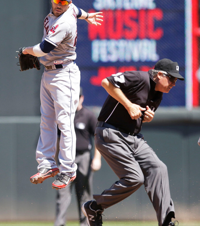 . Second base umpire Chris Conroy, right, ducks away as Cleveland second baseman Jason Kipnis jumps for a throw from center in an attempt to tag Minnesota\'s Brian Dozier, who  doubled in the seventh inning. (AP Photo/Jim Mone)
