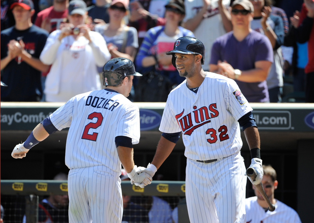 . Minnesota\'s Brian Dozier, left, celebrates with teammate Aaron Hicks after hitting a solo home run against Seattle during the seventh inning. (AP Photo/Craig Lassig)