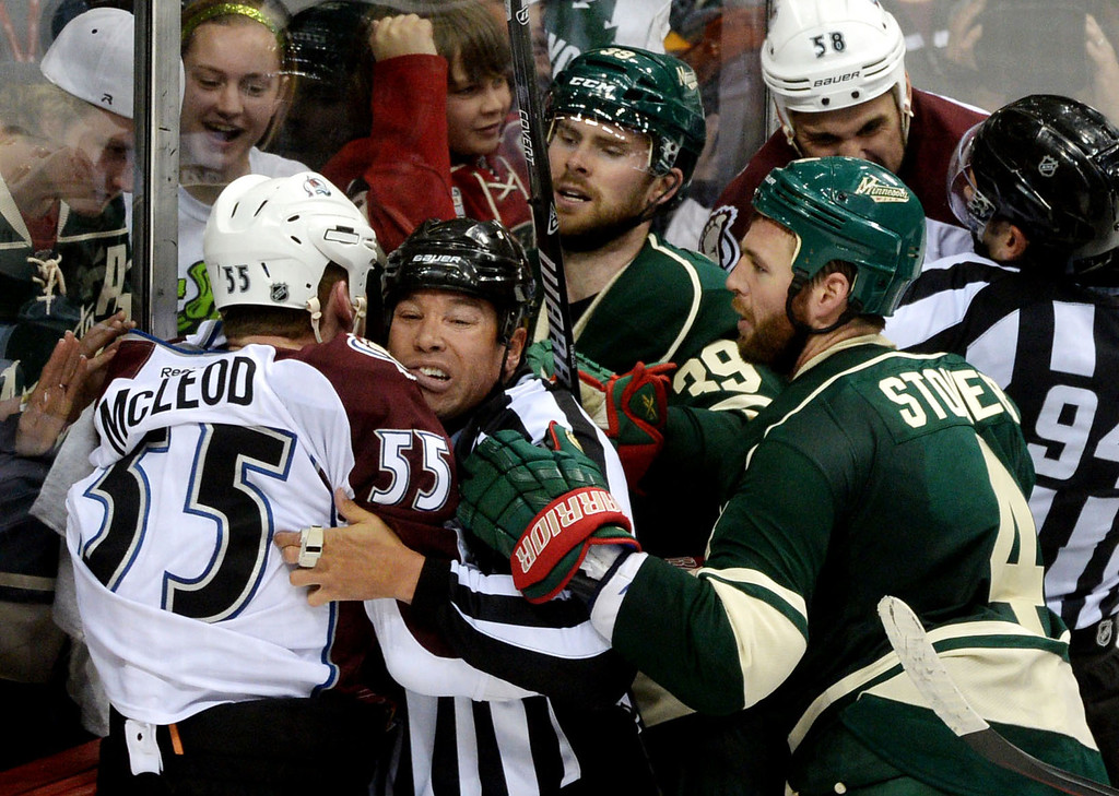. Colorado\'s Cody McLeod, left, goes after Minnesota\'s Clayton Stoner, right, and Nate Prosser as Linesman Jay Sharrers gets in the middle after the Wild won.  (Pioneer Press: Sherri LaRose-Chiglo)