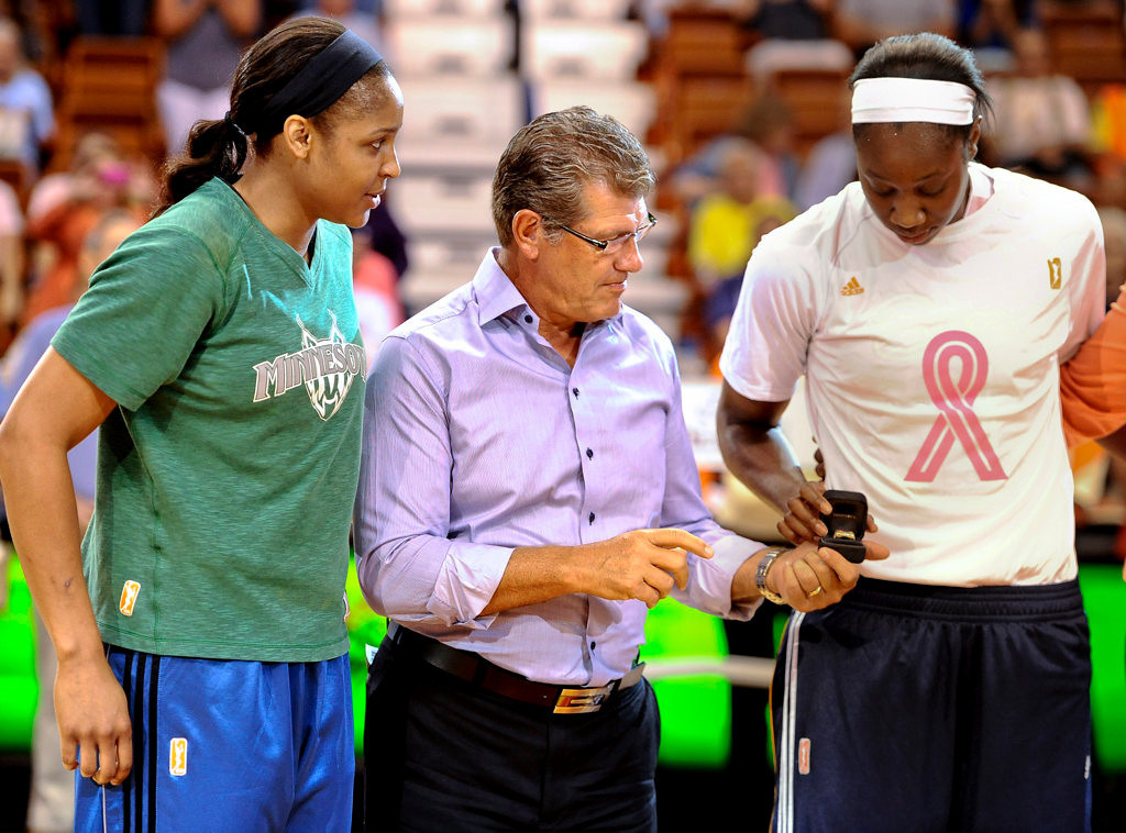 . Connecticut women\'s basketball coach Geno Auriemma, center, also coach of the U.S. women\'s national team, presents a ring in honor of the U.S. team\'s win in the Olympics last year to Connecticut Sun\'s Tina Charles, right, as former Sun teammate and current Minnesota Lynx player Maya Moore, left, watch during a ceremony before the game. USA basketball presented Olympic championship rings in person at every WNBA city that had players who participated on the gold medal team. (AP Photo/Jessica Hill)