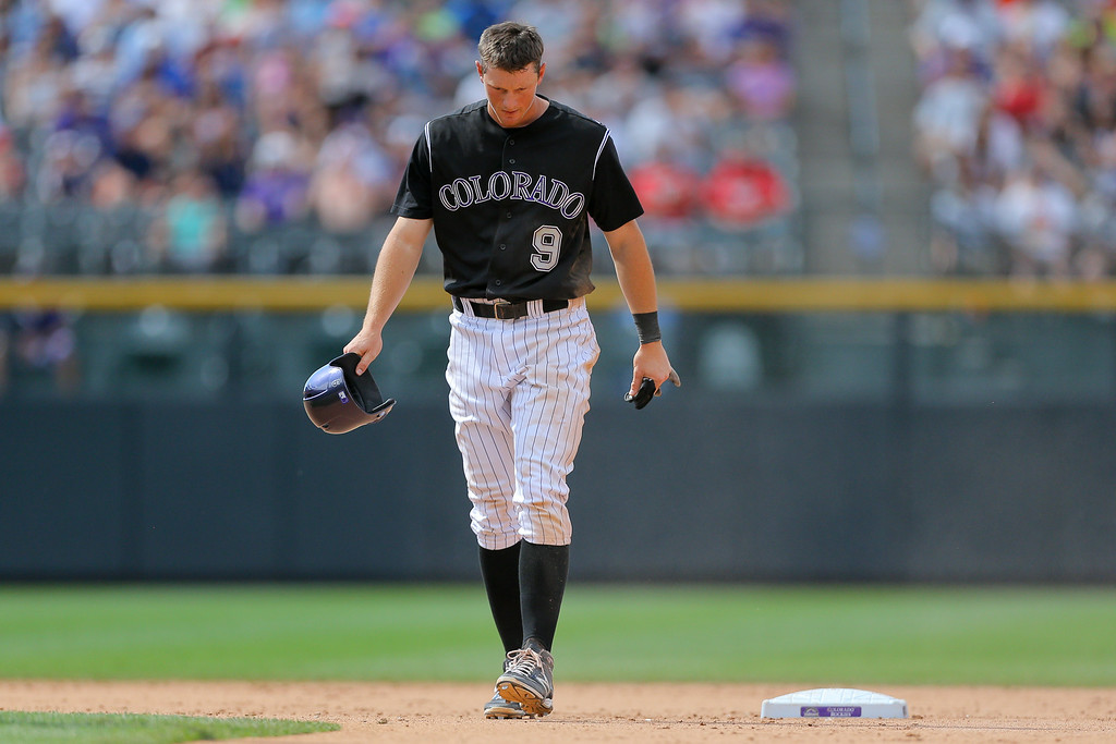 . DENVER, CO - JULY 13:  DJ LeMahieu #9 of the Colorado Rockies walks back to the dugout after getting caught stealing during the sixth inning against the Minnesota Twins at Coors Field on July 13, 2014 in Denver, Colorado. The Twins defeated the Rockies 13-5. (Photo by Justin Edmonds/Getty Images)