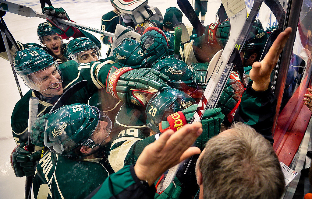 . Wild players swarm center Mikael Granlund against the glass after he scored the game-winning overtime goal against Colorado.  (Pioneer Press: Ben Garvin)