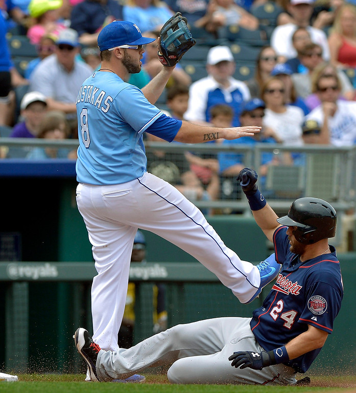 . The Minnesota Twins\' Trevor Plouffe (24) reaches third on a triple as Kansas City Royals third baseman Mike Moustakas (8) signals to hold the throw in the fifth inning. (John Sleezer/Kansas City Star/MCT)