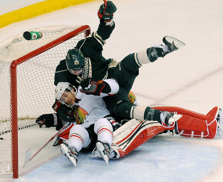 . Minnesota right wing Charlie Coyle, top, falls onto Chicago defenseman Duncan Keith and goalie Corey Crawford in the first period. (Pioneer Press: John Autey)