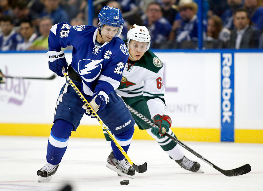 . Martin St. Louis #26 of the Tampa Bay Lightning avoids a check from Mikael Granlund #64 of the Minnesota Wild.  (Photo by Mike Carlson/Getty Images)