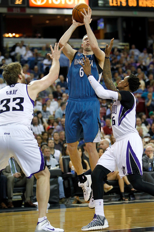 . Minnesota Timberwolves forward Robbie Hummel (6) shoots over Sacramento Kings defenders Aaron Gray (33) and Ben McLemore (16) during the first half of an NBA basketball game in Sacramento, Calif., on Sunday, April 13, 2014.(AP Photo/Steve Yeater)