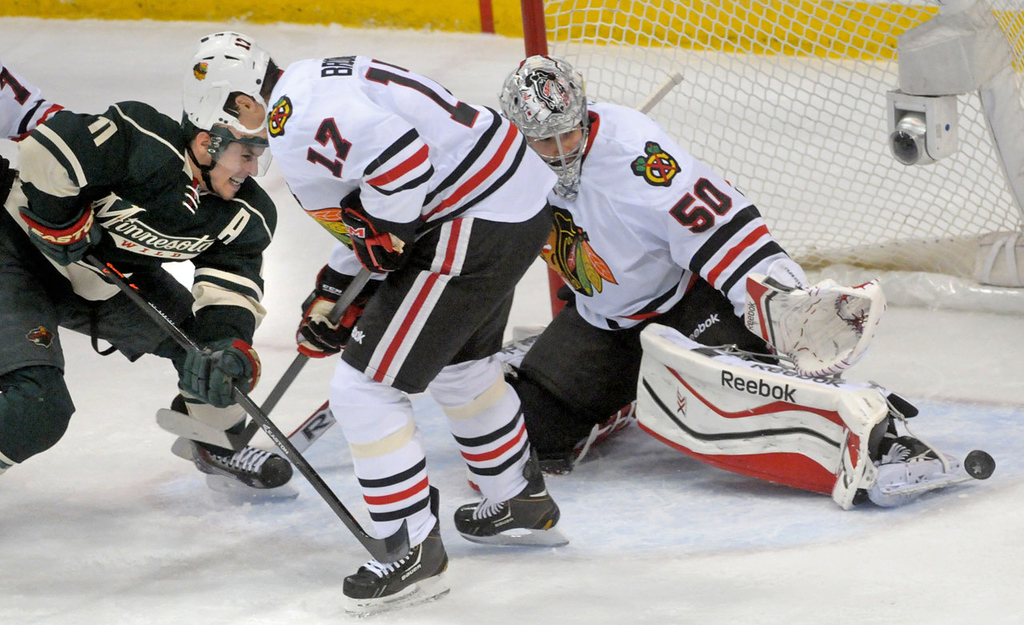 . Minnesota\'s Zach Parise, left, pushes a shot past Chicago defenseman Sheldon Brookbank, center, as Blackhawks goalie Corey Crawford gets a skate on the puck during the first period.   (Pioneer Press: Sherri LaRose-Chiglo)