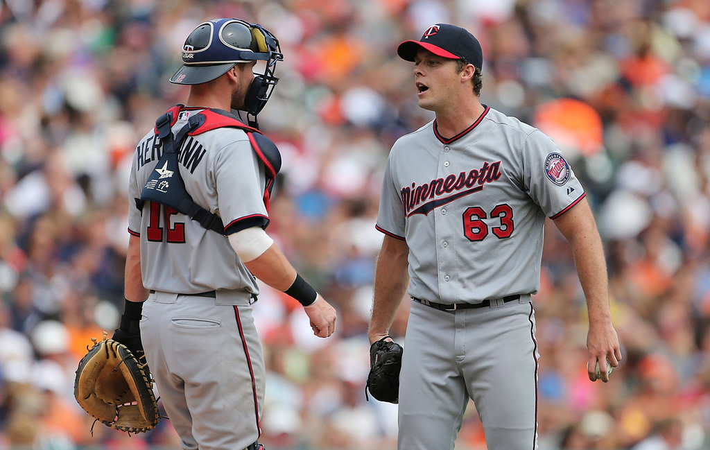 . Twins starter Andrew Albers, right, chats with catcher Chris Herrmann after Detroit\'s Prince Fielder singled (scoring Austin Jackson) during the third inning.  (Photo by Leon Halip/Getty Images)