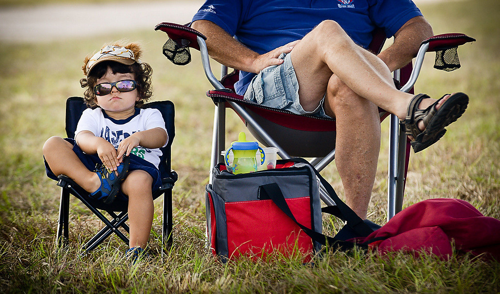 ". 2-year-old Avery Draper hunkers down next to his grandpa Bruce Draper, both of Ontario, Canada, as they watch players run drills during spring training at Hammond Stadium in Fort Myers, Fla., on Friday, February 21, 2014. ""He was a little whiny by the dugout,\"" said Bruce, who brought Avery to a quieter area. (Pioneer Press: Ben Garvin)"