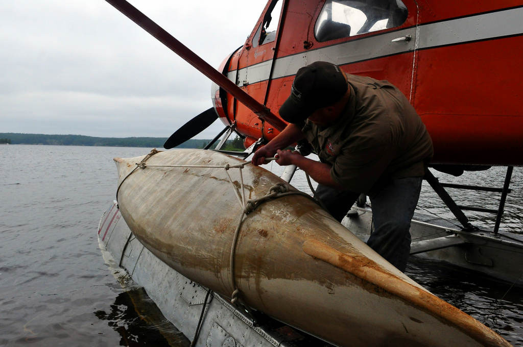 ". Matt Hooker, a pilot with Red lake, Ont.-based Viking Air secures a canoe to the pontoon of a floatplane in early July 2013 in Woodland Caribou Provincial Park in Ontario, Canada. ""You can break a canoe if you pull these knots too tight,\"" Hooker said. \""But I\'ve never had a canoe fall off.\""