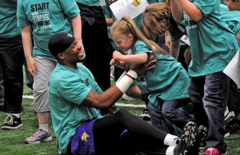 . Vikings wide receiver Jerome Simpson hoists Kayla Tillison, 9, from the Farmington Tigerpaws Special Olympics after practice. (Pioneer Press: Jean Pieri)