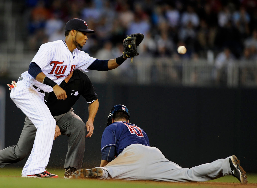 . Yan Gomes of the Cleveland Indians slides safely into second base as Twins shortstop Pedro Florimon fields the ball during the fifth inning. (Photo by Hannah Foslien/Getty Images)