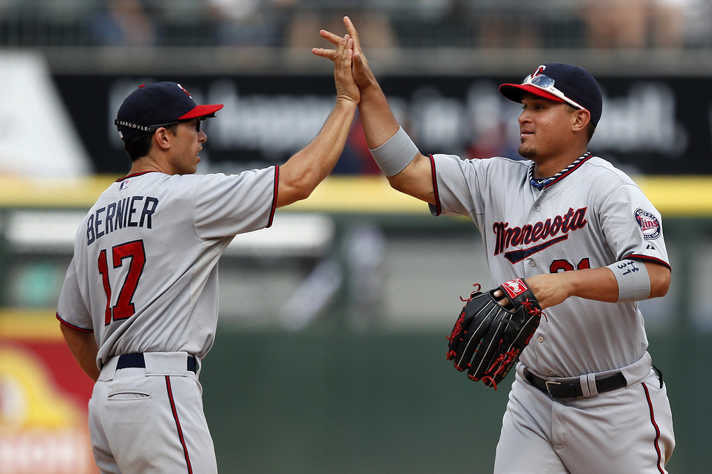 . Twins shortstop Doug Bernier, left, and left fielder Oswaldo Arcia celebrate their 5-2 victory over the White Sox. (AP Photo/Andrew A. Nelles)