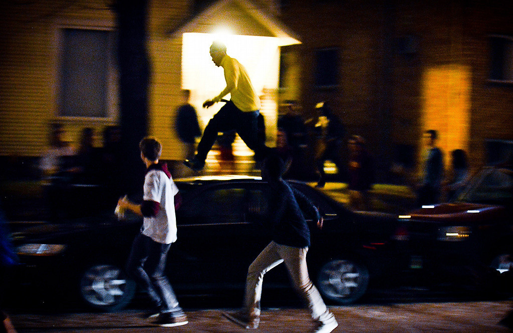 . Students run from car to car as they escape a line of riot police in the Dinkytown neighborhood. (Pioneer Press: Ben Garvin)