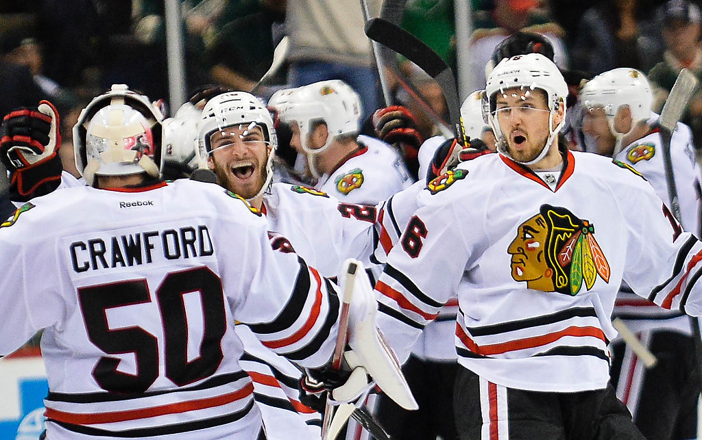 . Chicago Blackhawks goalie Corey Crawford is greeted by his teammates after Chicago won in overtime. (Pioneer Press: Ben Garvin)