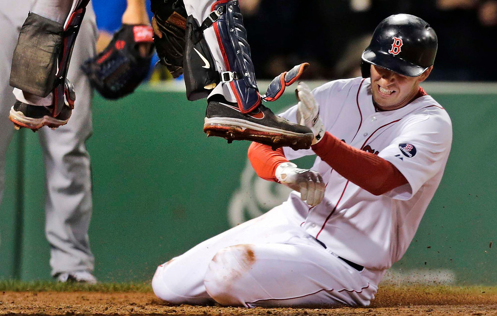 . Boston Red Sox\'s Stephen Drew, right, tries to beat a tag by Minnesota Twins catcher Joe Mauer on a double by Jacoby Ellsbury during the fifth inning of a baseball game at Fenway Park in Boston on Monday, May 6, 2013. Drew was out on the play. (AP Photo/Charles Krupa)