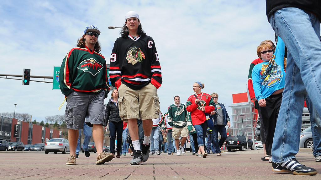 . A Wild fan and a Blackhawks fan cross West 7th Street at Kellogg Boulevard before the start of Game 3. (Pioneer Press: John Autey)