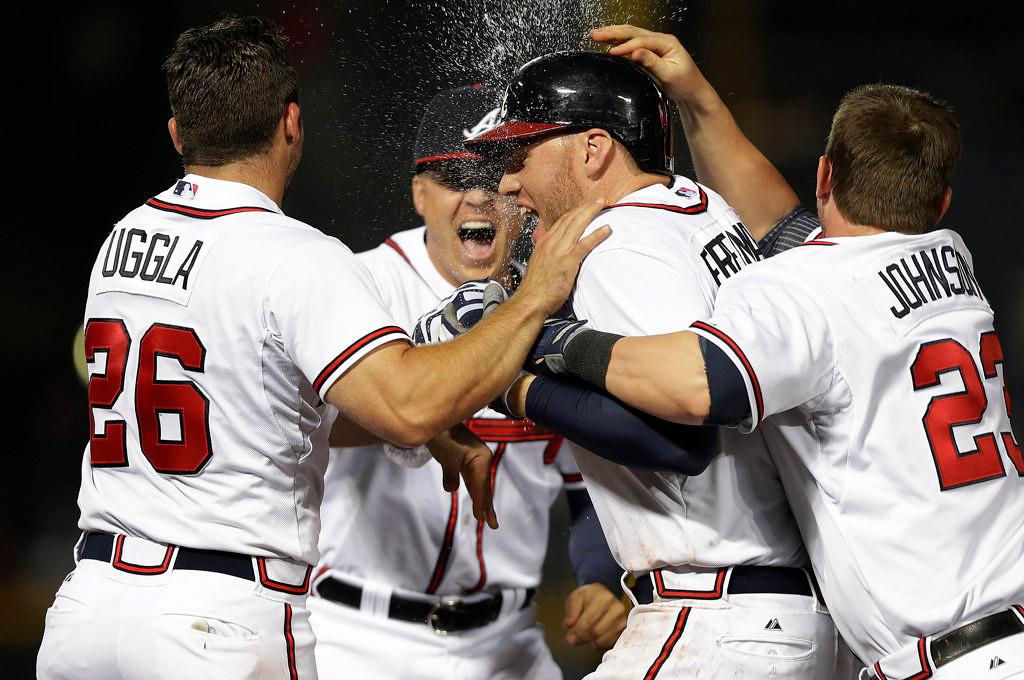 . Atlanta Braves first baseman Freddie Freeman, second from right, is mobbed by teammates Dan Uggle (26) Kris Medlen, and Chris Johnson, right, after driving in the game-winning run  with a base hit in the 10th inning of a baseball game against the Minnesota Twins Tuesday, May 21, 2013 in  in Atlanta. (AP Photo/John Bazemore)