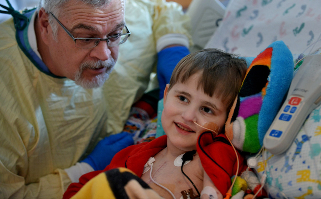 ". ""My name is Clifford, too,\"" said respiratory therapist Bob Clifford, left, who draws a smile from Cameron Ulrich as he watches his favorite cartoon, \""Clifford the Big Red Dog,\"" in his room.   (Pioneer Press: Richard Marshall)"