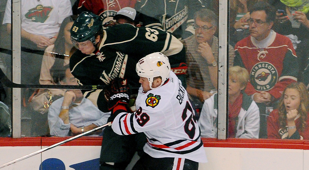 . Minnesota right wing Charlie Coyle, left, gets slammed against the glass by Chicago left wing Bryan Bickell (29) in the first  period. (Pioneer Press: John Autey)