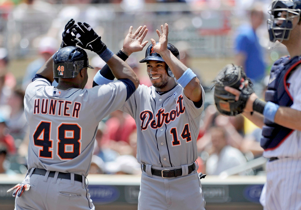 . Detroit\'s Austin Jackson, center, congratulates teammate Torii Hunter after Hunter knocked him in with his two-run home run as the Twins\' Joe Mauer looks on. (Photo by Hannah Foslien/Getty Images)