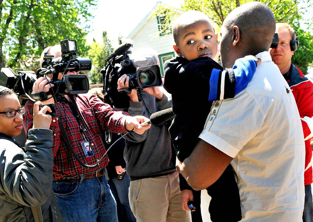 . Osman Kamara, a friend of the family of Zack Mohamed Fofana, holds his son Amadu, 2, as he talks with the media near St. Paul\'s Lilydale Park. (Pioneer Press: Jean Pieri)