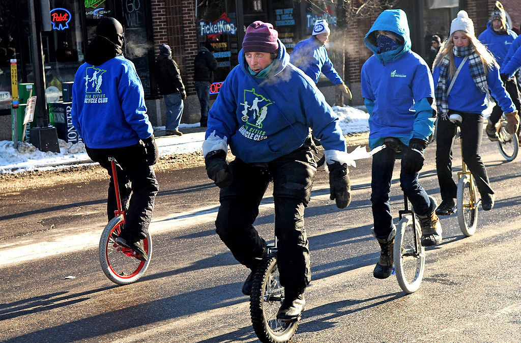 . A bundled up Twin Cities Unicycle Club try to stay warm during the Winter Carnival Grande Day Parade in St. Paul, Saturday January 25, 2014.  (Pioneer Press: Jean Pieri)