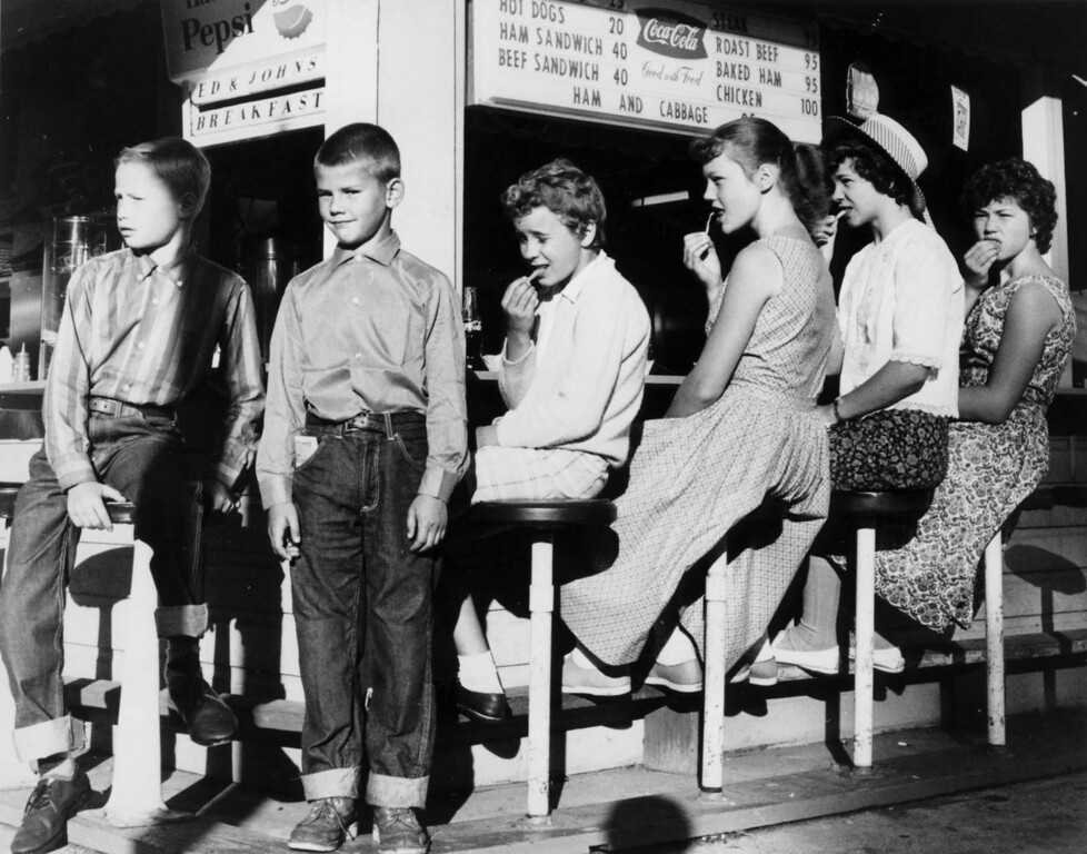 . Children eat fries while sitting at stools along an outdoor food booth at the Minnesota State Fair, circa 1950. Photo courtesy of the Minnesota State Fair.