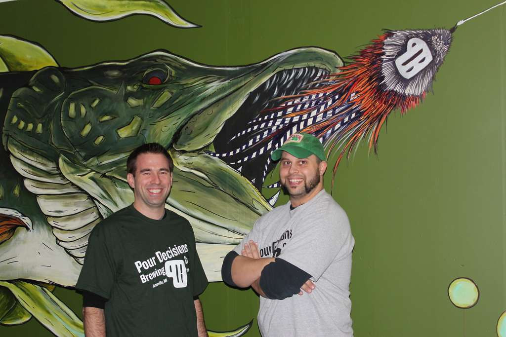 . Pour Decisions owners B.J. Haun, left, and Kristen England show off artwork on the taproom wall by local artist and friend Jake Keeler. England\'s 3-year-old son named the painted northern pike Laverne.