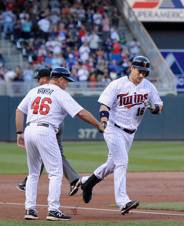 . Twins third base coach Joe Vavra congratulates Josh Willingham on his solo home run in the second inning. (Photo by Hannah Foslien/Getty Images)