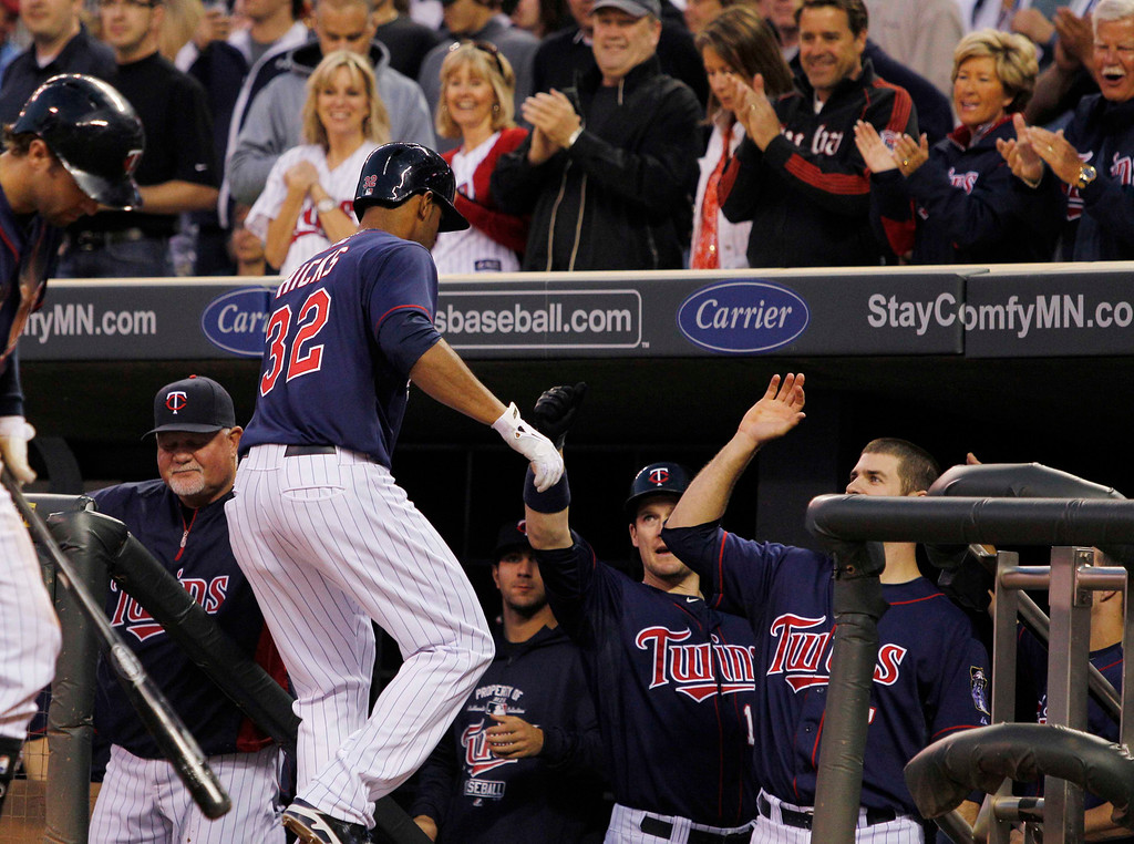 . Minnesota Twins\' Aaron Hicks (32) is congratulated by teammates after hitting a solo home run against Chicago White Sox starting pitcher Hector Santiago during the fourth inning of a baseball game, Monday, May 13, 2013, in Minneapolis. (AP Photo/Genevieve Ross)