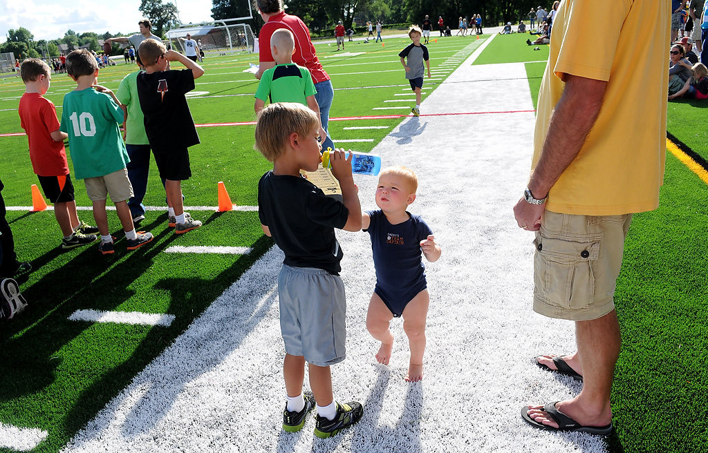 . Treyson Ditterich, 2, middle, gives his older brother Tanner, 6, left, a bottle of water while Tanner waits in line for football drills. (Pioneer Press: Sherri LaRose-Chiglo)
