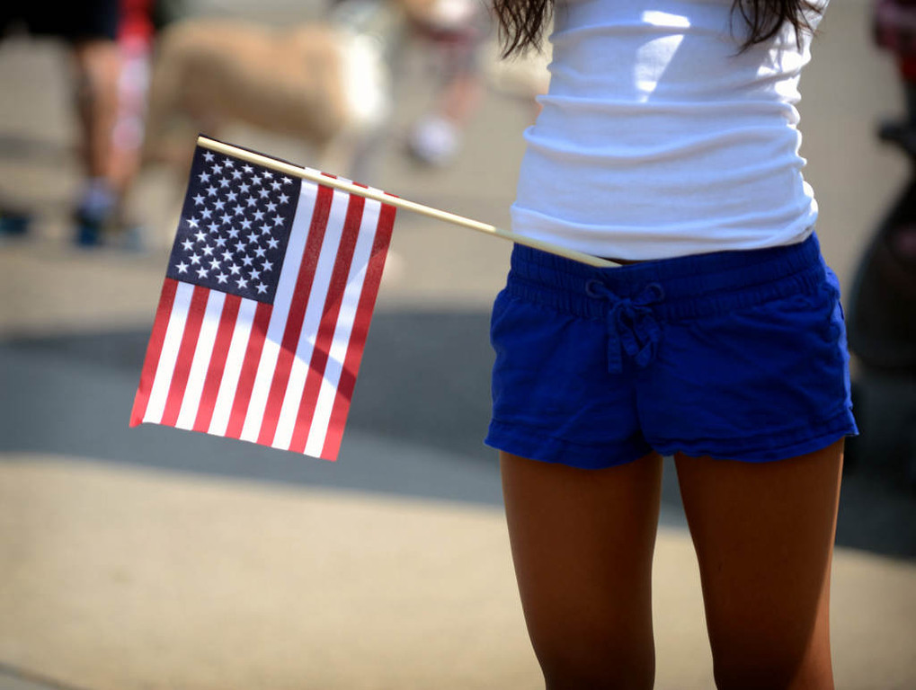 . A girl stands along Como Avenue in St. Paul waiting for the start of the parade. (Pioneer Press: Chris Polydoroff)