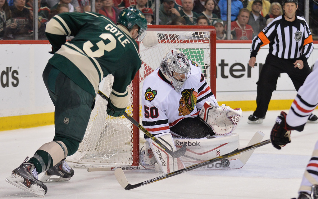 . Blackhawks goalie Corey Crawford makes a stick save on Minnesota\'s Charlie Coyle during the third period. (Pioneer Press: Ben Garvin)