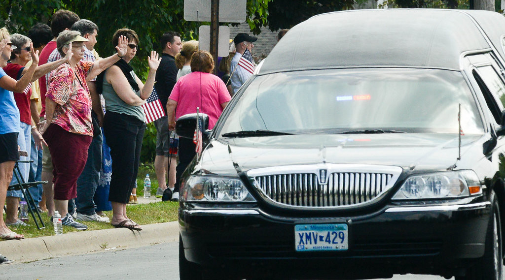 . People lined the streets to wave to the funeral procession, including the hearse and vehicles carrying family members.  (Pioneer Press: Ben Garvin)