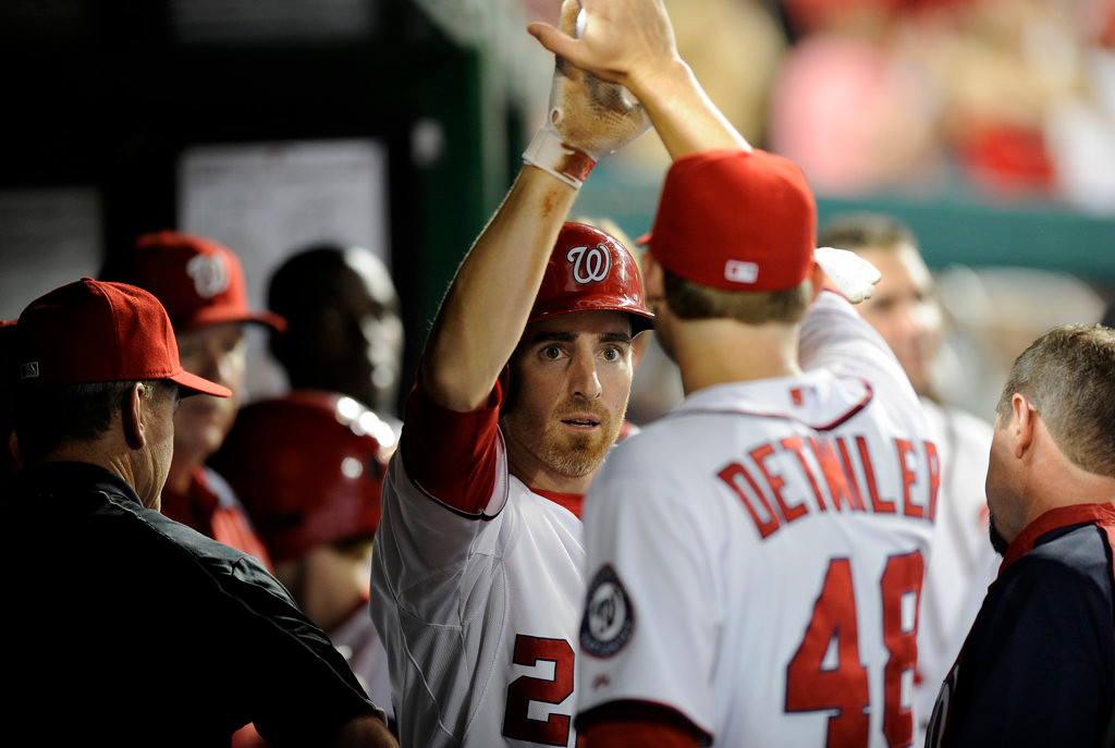 . Washington Nationals\' Adam LaRoche, left, gets a high five from teammate Ross Detwiler (48) in the dugout after he scored on a double by Ian Desmond during the seventh inning of the second baseball game of a day-night interleague doubleheader against the Minnesota Twins, Sunday, June 9, 2013, in Washington. The Nationals won 5-4. (AP Photo/Nick Wass)