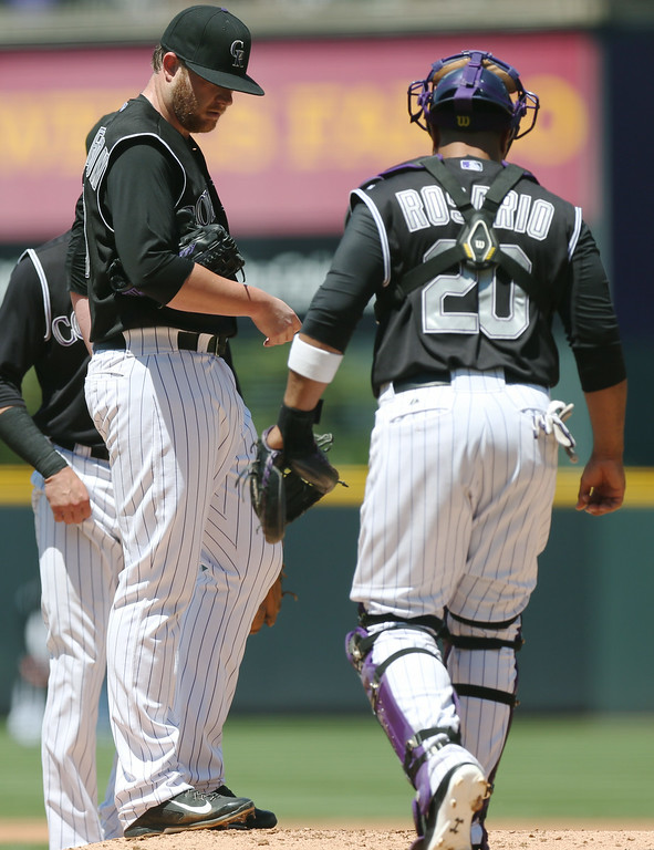 . Colorado Rockies starting pitcher Brett Anderson, left, confers with catcher Wilin Rosario after Anderson gave up a double to bring in two runs to Minnesota Twins\' Eduardo Escobar in the first inning. (AP Photo/David Zalubowski)