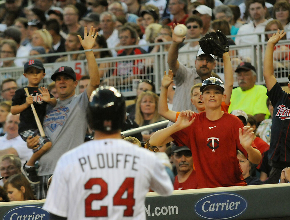 . Minnesota third baseman Trevor Plouffe tosses a ball to excited fans. (Pioneer Press: John Autey)