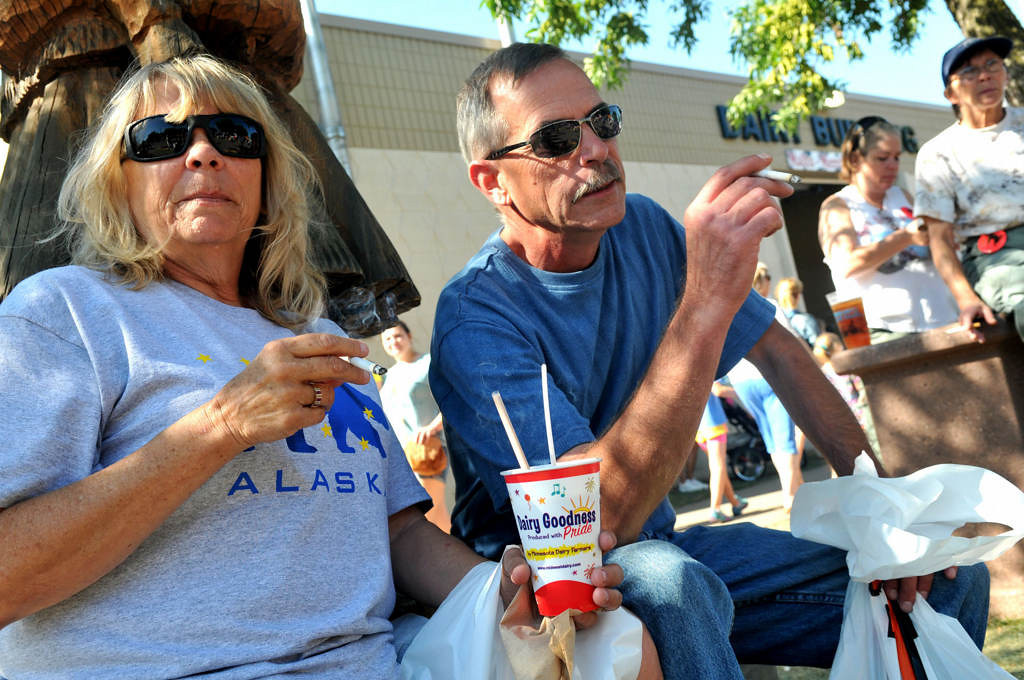 """. Curt Kadlec, right, of Anoka, though it \""""was really nice that the State Fair folks put up the stations throughout the Fairgrounds,\"""" this one in front of the Dairy Building. At left, his sister Chris Benson of Burnsville enjoys her cigarette with a Dairy Building milkshake. (Pioneer Press: John Doman)"""