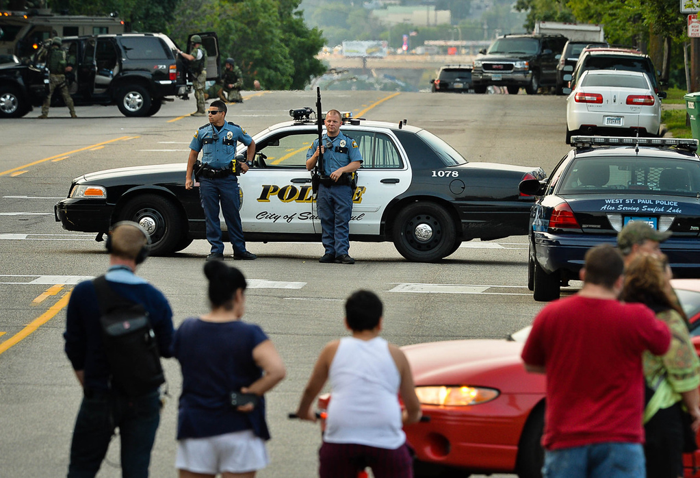 . St. Paul Police officers block off Robert Street in St. Paul after the suspect\'s car was found at a home on Wednesday. (Pioneer Press: Ben Garvin)