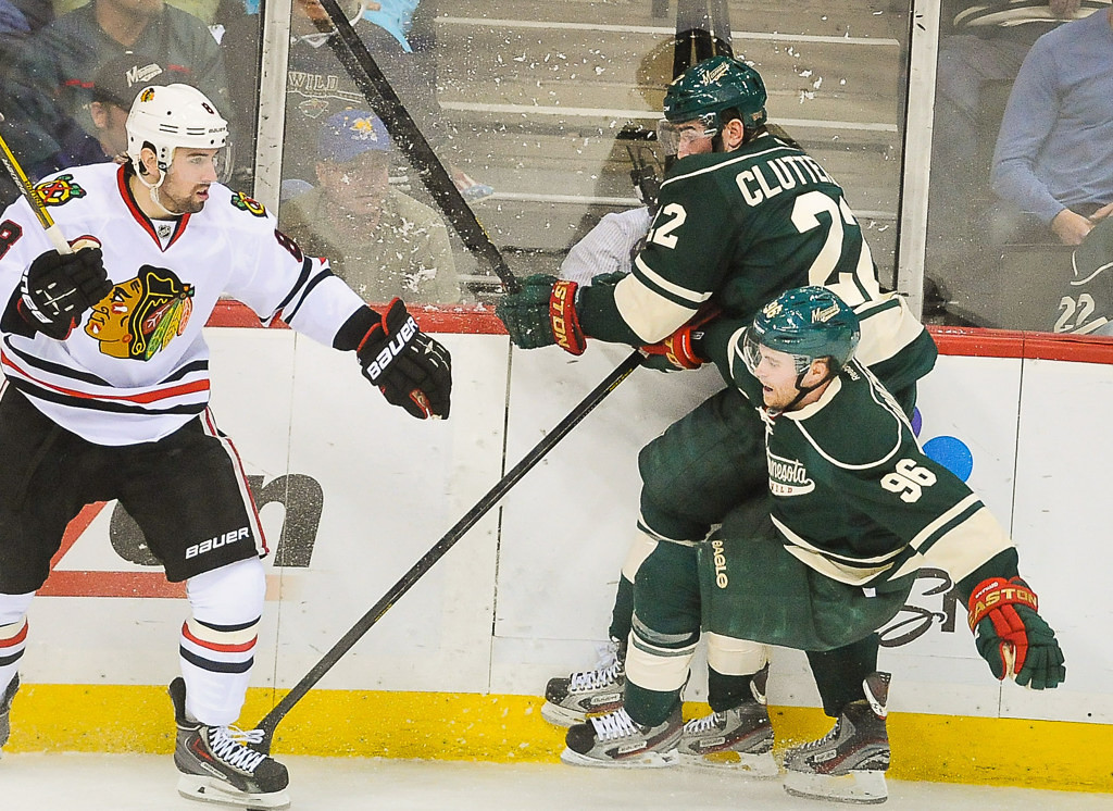 . Minnesota\'s Cal Clutterbuck, top, collides with teammate Pierre-Marc Bouchard  in the third period. At left is Chicago\'s Nick Leddy. (Pioneer Press: Ben Garvin)
