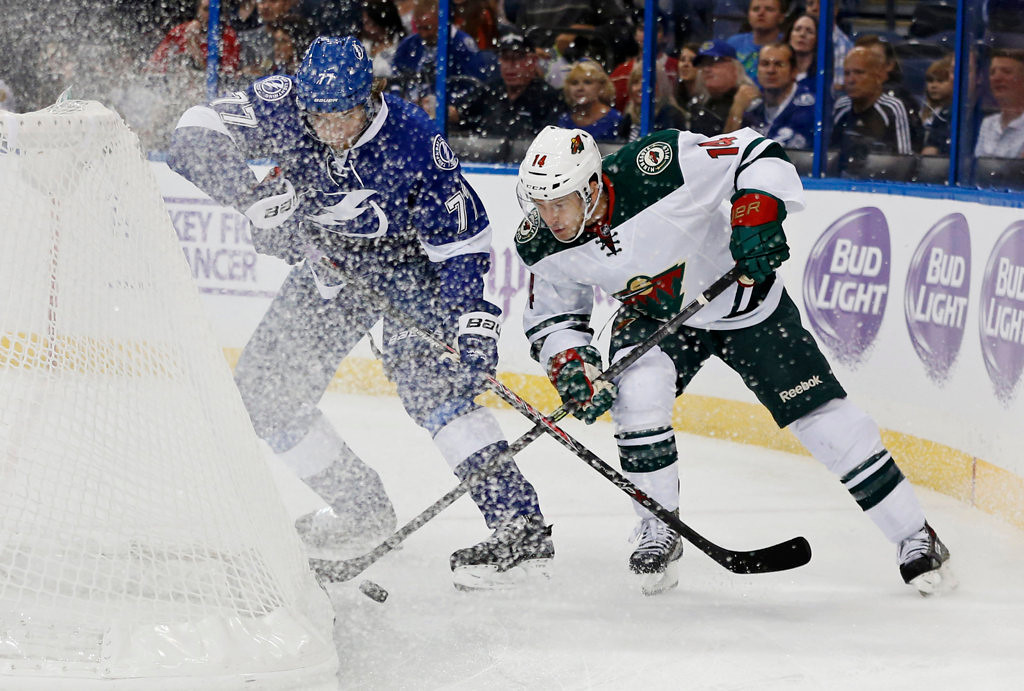 . Victor Hedman #77 of the Tampa Bay Lightning and Justin Fontaine #14 of the Minnesota Wild battle for a loose puck. (Photo by Mike Carlson/Getty Images)